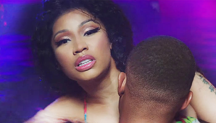 """Nicki Minaj is Back with Racy New 'Megatron' Video – See it Here! Last week Nicki Minaj broke her three-month social media blackout with new information on upcoming music, and today she has finally released the video for her brand-new song 'Megatron', ushering in what might be the party song of the summer and a new era of Minaj music domination. The Video Itself Calling it 'Racy' probably doesn't do the video justice, which features Minaj in a variety of outfits and settings, including several tiny string bikinis. She is seen with a muscle-bound man in a sauna and a pool, and several clips show him groping her, holding her to his chest or standing in suggestive positions. Nicki has never been one to shy away from controversy or her own sexuality, and given the lyrics to the song, no one should be surprised by the video. A keen eye will notice there is very little product placement in the video itself. Many popular artists like Minaj will take money from companies to feature their products – new Samsung Galaxy phones and Beats headphones are very popular right now in videos – but the only real placement that is seen is her own brand of Moscato, MYX. She even references the alcohol in her lyrics, saying """"I own my own Moscato, b****, we getting' drunk-drunk"""". Nicki Has Been Busy If you feel like Minaj just released a CD, you're not wrong. Her fourth studio album Queen came out August of 2018, meaning that it has been less than a full year and she is already putting out new music. The time between the release of The Pinkprint and Queen was four years. Many artists pace themselves more, giving more time to tour or create. Not Minaj, who jumped into the studio full force. While Megatron is Nicki's first new solo music this year, she has been featured on a number of other tracks by big name artists, including an interesting collaboration with Avril Lavigne and a popular hit with Chris Brown. Nicki also toured this year, doing 19 shows on her The Nicky Wrld Tour. She starte"""