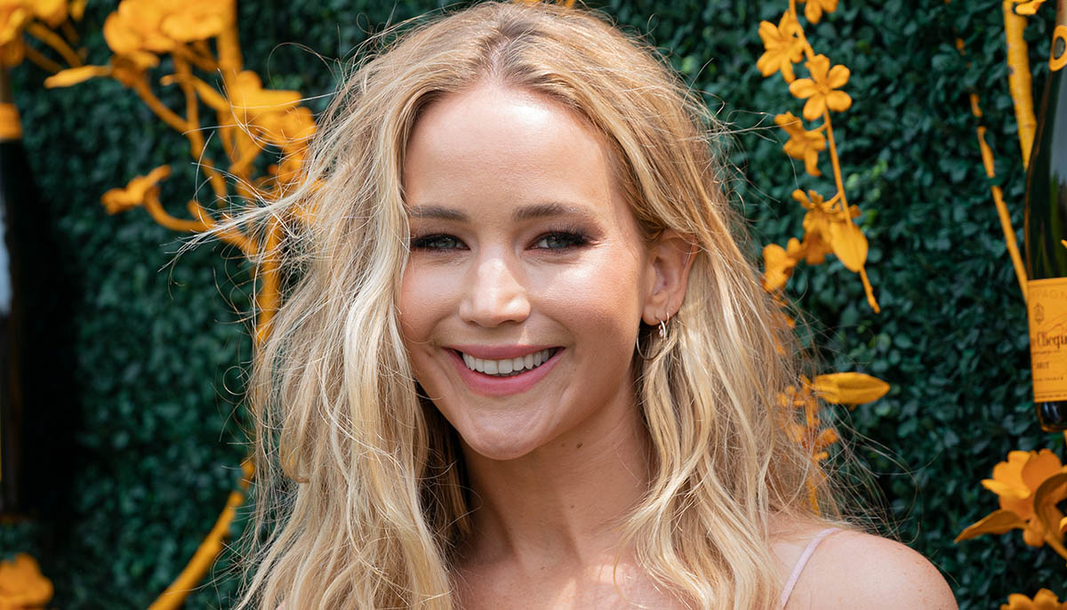 Jennifer Lawrence smiling in front of shrubs and flowers.
