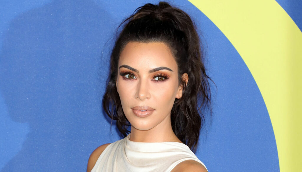 kim kardashian in high neck white top against blue and yellow background