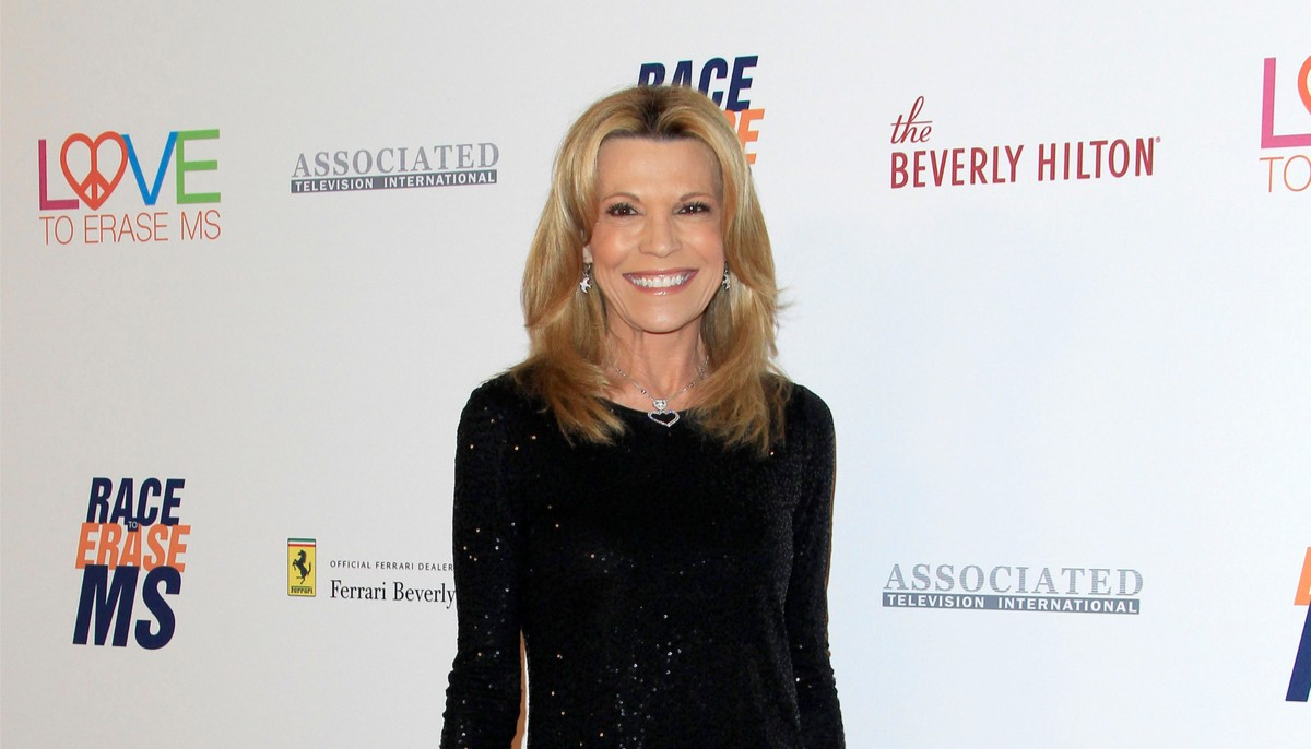 Vanna white wearing a black sparkling dress smiling on the red carpet