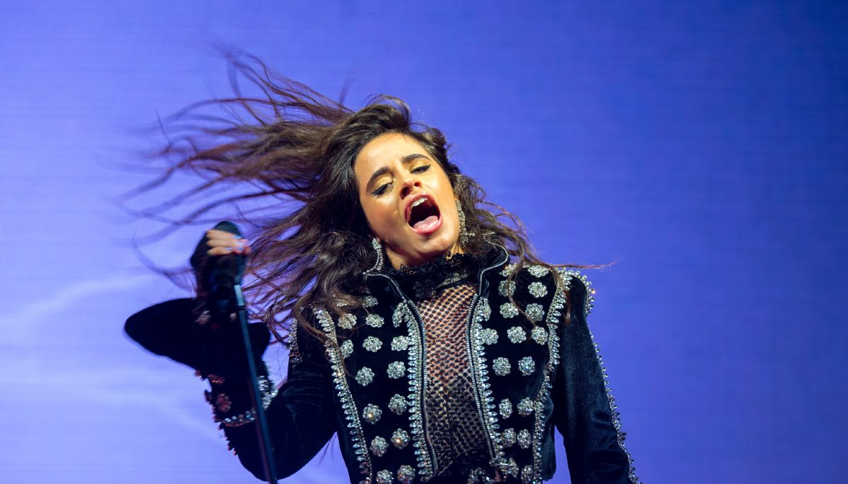 camila cabello singing on stage, flipping her hair and holding a mic