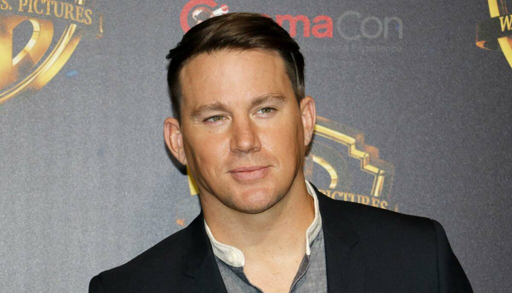 actor channing tatum wearing a black jacket and grey shirt on the red carpet at an event