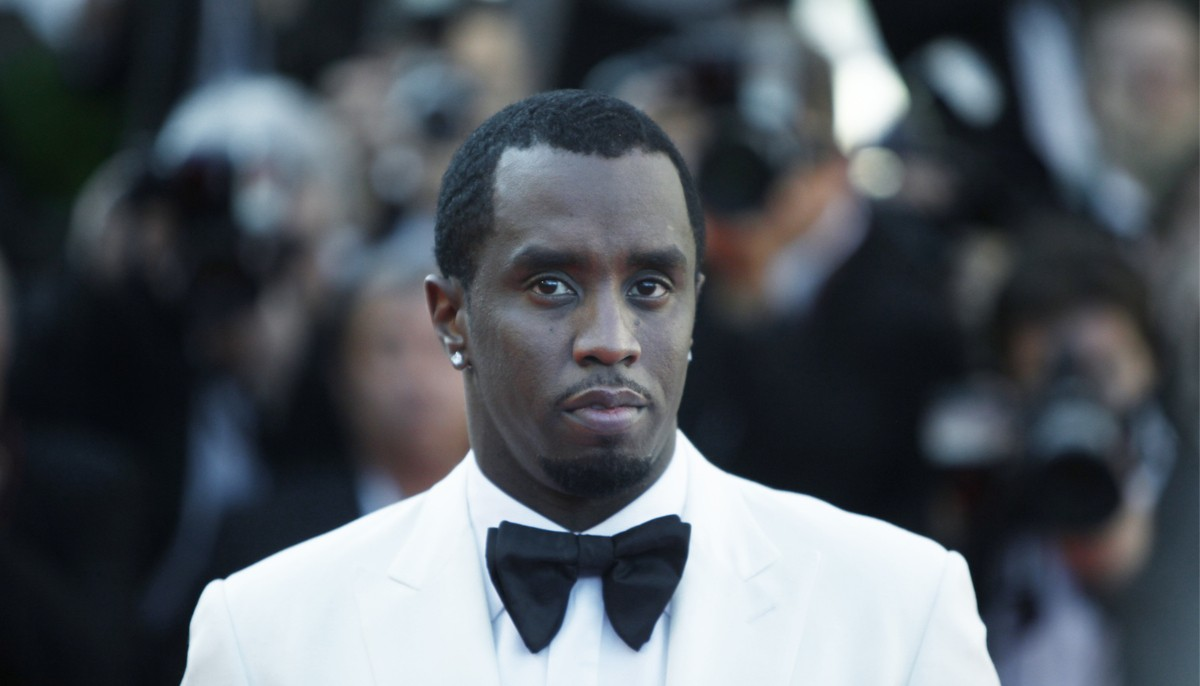 diddy dressed in a white suit with a black bow tie, looking unimpressed at the camera