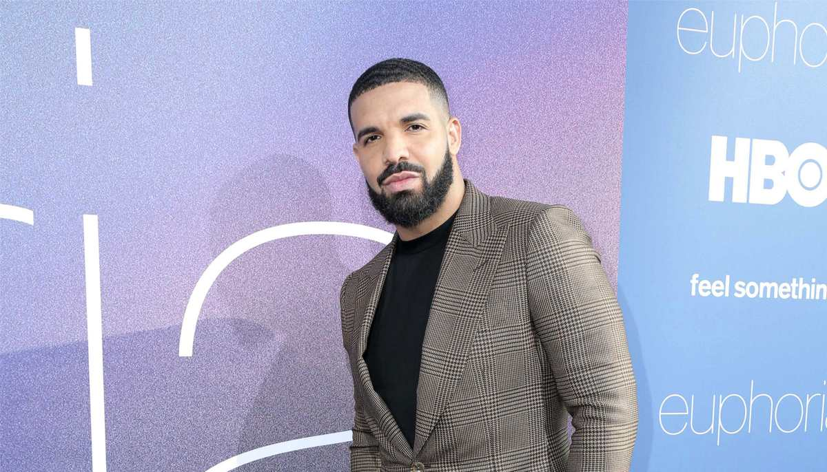 drake standing on the red carpet wearing a grey suit jacket and black shirt