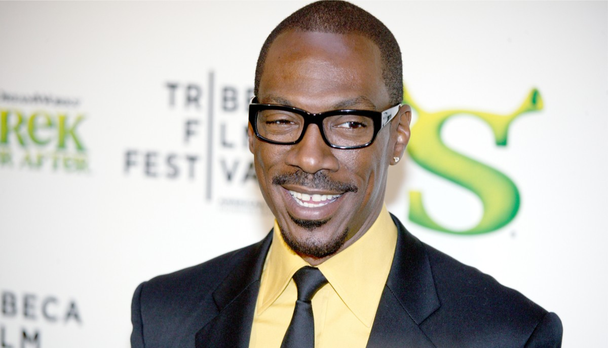 eddie murphy smiling on the red carpet for a shrek movie wearing a dark suit and yellow shirt