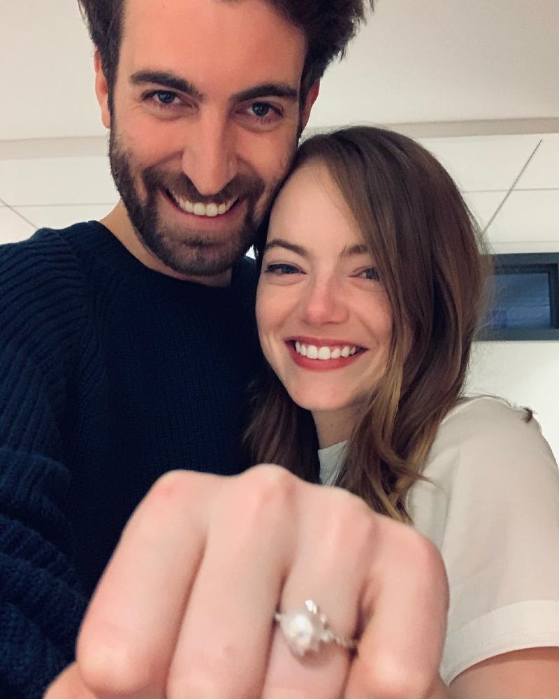 emma stone and dave mccary smiling at the camera with emma stones engagement ring in the front