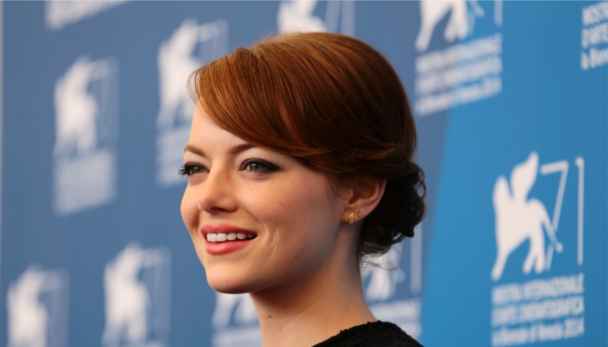 emma stone with her hair pulled back, smiling off camera at a red carpet event