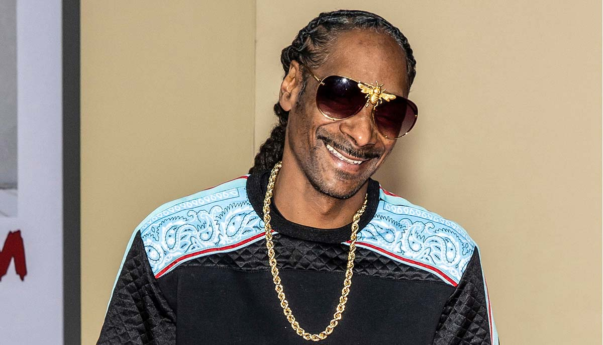 rapper snoop dog smiling and wearing sunglasses with golden bee and a gold chain