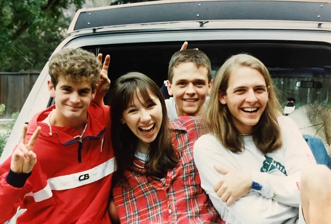 young Alexandra Grant with three friends smiling and standing in front of a car