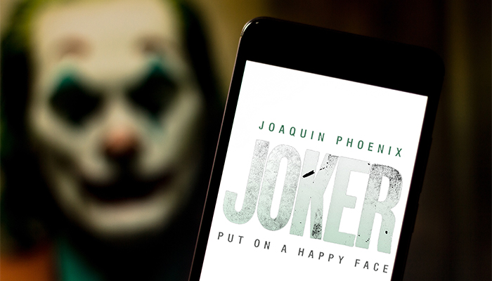 iPhone in front of a screen with Joaquin Pheonix's Joker character on it