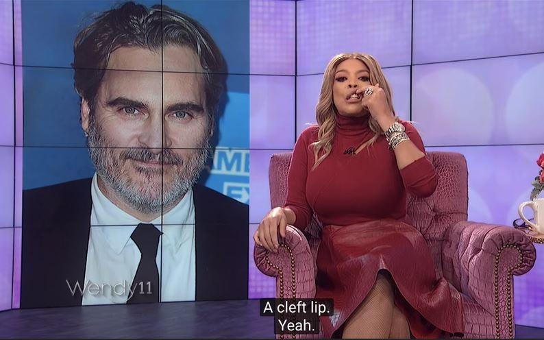 a still from the wendy williams show where she is lifting her lip to mock joaquin phoenixs lip scar