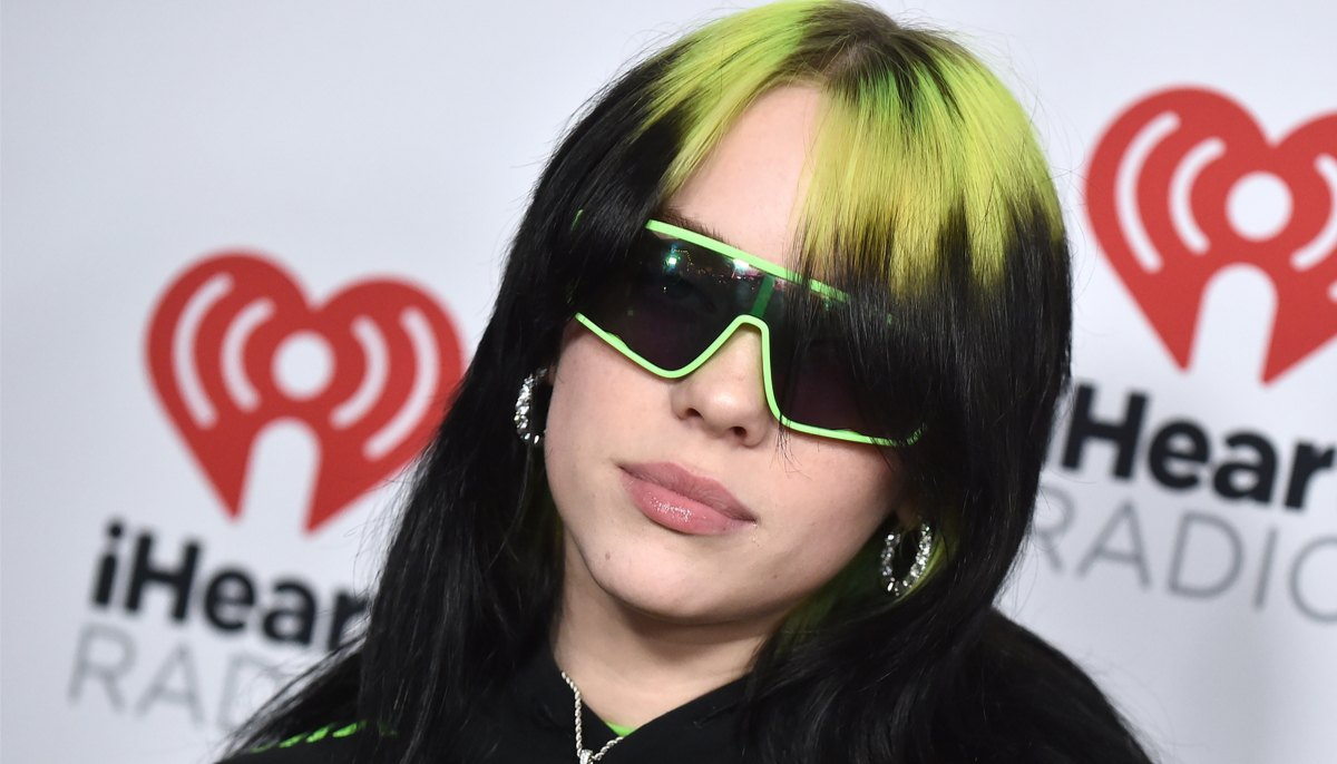 billie eilish with her green hair and matching green and black sunglasses on the red carpet