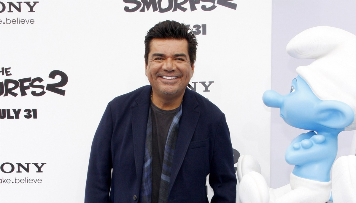 george lopez standing on the red carpet of a smurf event and smiling