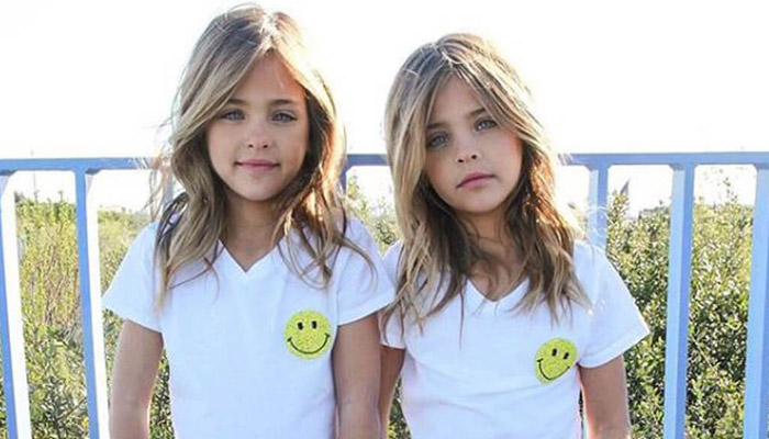 Clements twins pose in matching white tshirts with smiley faces on them.